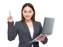 Empresaria mezclada asiática con el ordenador portátil y el finger para arriba Fotos de archivo libres de regalías