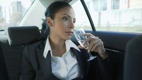 Empresaria mezclada que se sienta en el asiento trasero del coche con el champán, celebración metrajes