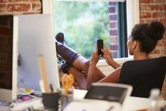 Empresaria On Mobile Phone que se relaja en oficina moderna Fotos de archivo