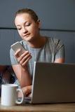 Empresaria With Mobile Phone que trabaja en el ordenador portátil en Internet Ca Imagen de archivo libre de regalías