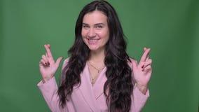 Empresaria morena en chaqueta rosada que gesticula muestras de los cruzar-fingeres de mostrar esperanza en cámara en fondo verde almacen de video