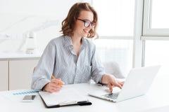Empresaria morena feliz en vidrios usando wh del ordenador portátil Imágenes de archivo libres de regalías