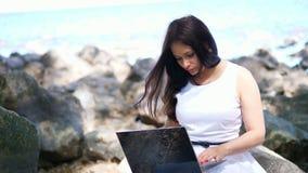 Empresaria morena hermosa en el vestido blanco, sentándose en piedras y trabajando en el ordenador portátil al aire libre, ordena metrajes