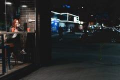 Empresaria, muchacha que trabaja en el ordenador port?til en el caf?, smartphone en manos, pluma, tel?fono del control del uso El foto de archivo