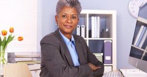 Empresaria negra que se sienta en la sonrisa del escritorio Imágenes de archivo libres de regalías