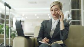 Empresaria ocupada rubia que se sienta en butaca en el pasillo del hotel que habla el teléfono móvil, escribiendo en libreta y us almacen de video