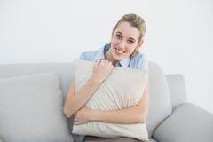 Empresaria pacífica contenta que se sienta en el sofá que sostiene una almohada Imagen de archivo