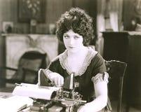 Empresaria pensativa con la máquina de escribir en el escritorio en oficina imagen de archivo