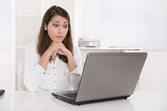 Empresaria pensativa delante de su ordenador en la oficina. imagenes de archivo