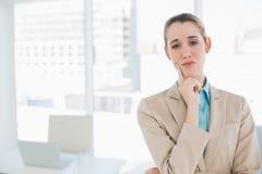 Empresaria pensativa elegante que presenta en su oficina Fotografía de archivo