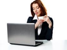 Empresaria pensativa que se sienta en la tabla con el ordenador portátil Foto de archivo libre de regalías