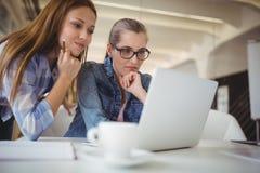 Empresaria pensativa que trabaja en el ordenador portátil con el colega en oficina Foto de archivo libre de regalías