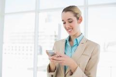 Empresaria ponytailed atractiva que manda un SMS con su smartphone Foto de archivo