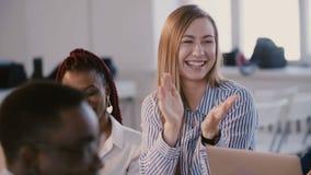 Empresaria positiva feliz joven que ríe, aplaudiendo mientras que escucha el coche del negocio que habla en el seminario del neg almacen de video