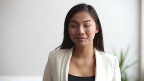 Empresaria profesional asiática joven que mira la cámara en oficina almacen de video