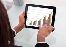 Empresaria que analiza el gráfico de la comparación imagen de archivo