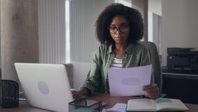 Empresaria que analiza el gráfico y que mecanografía en el ordenador portátil almacen de video