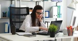 Empresaria que bosteza y que usa el ordenador portátil en oficina moderna almacen de video