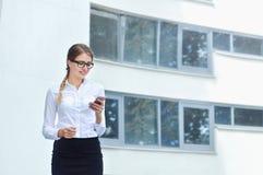 Empresaria que camina en la calle de la ciudad usando un teléfono elegante Imagen de archivo libre de regalías