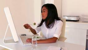 Empresaria que come el almuerzo en su escritorio almacen de metraje de vídeo