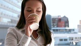 Empresaria que come el café a ir afuera almacen de metraje de vídeo