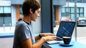 Empresaria que come un café del od de la taza mientras que usa el ordenador portátil metrajes