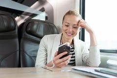 Empresaria que comunica en el teléfono móvil mientras que viaja en tren Fotografía de archivo