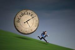 Empresaria que corre con el reloj grande del plazo imagen de archivo