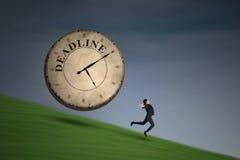 Empresaria que corre con un reloj del plazo foto de archivo