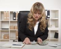 Empresaria que cuenta hacia fuera el dinero en su escritorio Foto de archivo libre de regalías