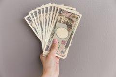 Empresaria que da el dinero y que sostiene el dinero de 10.000 yenes japoneses disponible en el fondo gris de la pared, yen japon Imagen de archivo libre de regalías