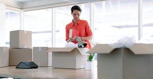 Empresaria que desempaqueta pertenencia de la oficina de las cajas de cartón en la tabla foto de archivo libre de regalías