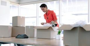 Empresaria que desempaqueta pertenencia de la oficina de las cajas de cartón en la tabla imágenes de archivo libres de regalías
