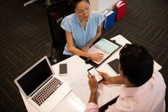 Empresaria que discute con el colega masculino en el escritorio Fotografía de archivo libre de regalías