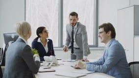 Empresaria que discute informes con los colegas masculinos y femeninos que se sientan en la tabla en oficina moderna