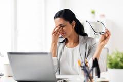 Empresaria que frota ojos cansados en la oficina Foto de archivo libre de regalías