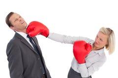 Empresaria que golpea al colega con sus guantes de boxeo Foto de archivo libre de regalías