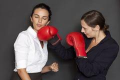 Empresaria que golpea otra con los guantes de boxeo Fotografía de archivo