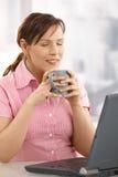 Empresaria que goza de té en el escritorio Imágenes de archivo libres de regalías