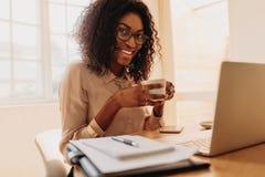 Empresaria que goza de una taza de café mientras que trabaja en el ordenador portátil a fotos de archivo