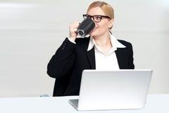 Empresaria que goza del café en el escritorio del trabajo Imágenes de archivo libres de regalías