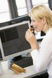 Empresaria que goza del emparedado durante descanso del almuerzo Foto de archivo libre de regalías
