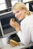 Empresaria que goza del emparedado durante descanso del almuerzo Imágenes de archivo libres de regalías
