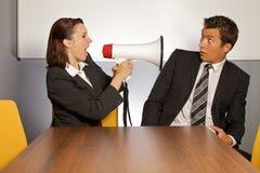 Empresaria que grita en el hombre de negocios a través del megáfono Imagen de archivo
