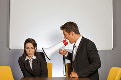 Empresaria que grita en el hombre de negocios a través del megáfono Foto de archivo