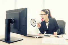 Empresaria que grita en megáfono foto de archivo