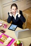 Empresaria que habla con dos teléfonos Fotografía de archivo libre de regalías