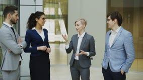 Empresaria que habla con sus colegas mientras que se coloca en pasillo de la oficina Grupo de hombres de negocios que discuten el almacen de video