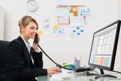 Empresaria que habla en el teléfono en el escritorio Fotografía de archivo libre de regalías