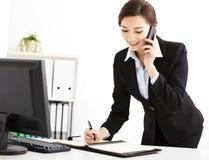 Empresaria que habla en el teléfono en oficina foto de archivo libre de regalías